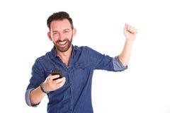 Hombre maduro con el teléfono móvil que celebra éxito Imágenes de archivo libres de regalías