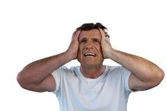 Hombre maduro con la cabeza a disposición que sufre de dolor de cabeza Fotos de archivo