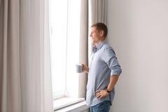 Hombre maduro con la taza de bebida cerca de la ventana con las cortinas abiertas en casa imagen de archivo