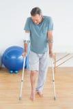 Hombre maduro con las muletas en el hospital del gimnasio Foto de archivo