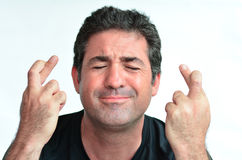 Hombre maduro con los fingeres cruzados que espera suerte Foto de archivo libre de regalías