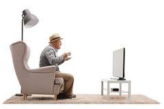 Hombre maduro con una taza que se sienta en una butaca y un televi de observación Imagenes de archivo