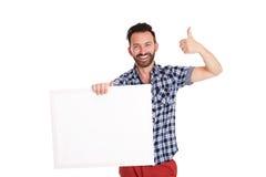 Hombre maduro confiado que sostiene el cartel en blanco y que muestra los pulgares para arriba Fotos de archivo