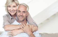 Hombre maduro de abarcamiento sonriente de la mujer de detrás en el sofá Fotos de archivo libres de regalías