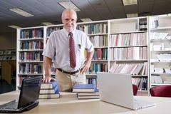 Hombre maduro en el vector de la biblioteca con los libros de textos Fotos de archivo libres de regalías
