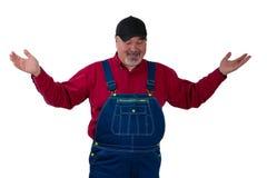 Hombre maduro en guardapolvos que gesticula con las palmas aumentadas Imagen de archivo libre de regalías