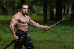 Hombre maduro en la acción con la espada Foto de archivo libre de regalías