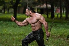 Hombre maduro en la acción con la espada Imagenes de archivo