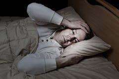 Hombre maduro en la cama muy enferma Fotografía de archivo
