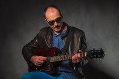 Hombre maduro en la chaqueta de cuero que toca la guitarra Foto de archivo