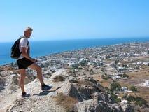 Hombre maduro encima de la montaña Isla de Santorini, Grecia imagenes de archivo