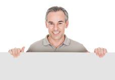 Hombre maduro feliz que se coloca detrás de cartel Fotos de archivo libres de regalías