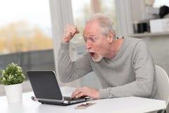 Hombre maduro feliz que tiene una buena sorpresa en el ordenador portátil foto de archivo