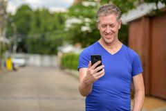 Hombre maduro feliz usando el teléfono en las calles al aire libre fotos de archivo libres de regalías