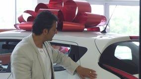 Hombre maduro hermoso feliz que muestra los pulgares para arriba después de comprar un coche almacen de metraje de vídeo
