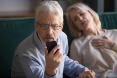 Hombre maduro, marido que llama la emergencia, mujer, esposa que tiene ataque del corazón fotografía de archivo