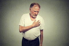 Hombre maduro mayor que sufre de mún dolor en su ataque del corazón al pecho imagen de archivo libre de regalías