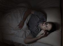 Hombre maduro no capaz de caer dormido durante noche Imagenes de archivo