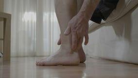 Hombre maduro paciente con la artritis que se sienta en cama y que frota su tobillo y pie que alivian el dolor almacen de video
