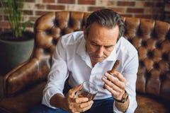 Hombre maduro pensativo con el alcohol ambarino Imagen de archivo libre de regalías