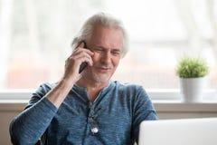 Hombre maduro positivo que se sienta en la tabla que habla en el teléfono imagenes de archivo