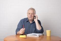 Hombre maduro preocupante en un funcionamiento del teléfono Imagen de archivo libre de regalías