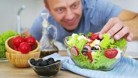 Hombre maduro preparando ensalada de verduras frescas en su cocina. Vídeo en cámara lenta en cámara de cine mágico negro de 6  almacen de metraje de vídeo