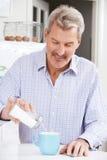 Hombre maduro que añade a Sugar To Cup Of Coffee Fotos de archivo