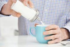 Hombre maduro que añade a Sugar To Cup Of Coffee Foto de archivo