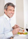 Hombre maduro que almuerza en casa fotografía de archivo