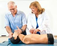 Hombre maduro que aprende el CPR foto de archivo