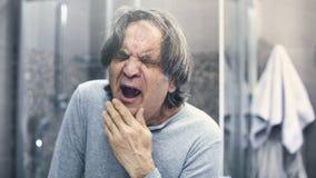 Hombre maduro que bosteza en cuarto de baño imagen de archivo libre de regalías