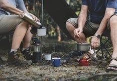 Hombre maduro que cocina en un sitio para acampar imagenes de archivo