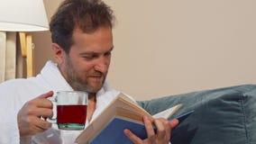 Hombre maduro que come té caliente aromático, leyendo un libro en casa, llevando la albornoz almacen de metraje de vídeo