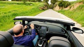 Hombre maduro que conduce el coche de deportes convertible almacen de metraje de vídeo