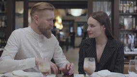 Hombre maduro que cuenta historia a una mujer joven hermosa en la tabla del restaurante almacen de metraje de vídeo