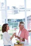 Hombre maduro que da la flor a la mujer Imagenes de archivo