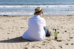 Hombre maduro que descansa con el vino en la playa en verano Imagenes de archivo