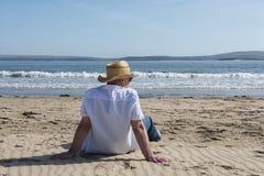 Hombre maduro que descansa sobre la playa en verano Foto de archivo