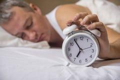Hombre maduro que duerme en cama con el despertador en primero plano en la cama imagen de archivo