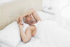 Hombre maduro que duerme en cama en casa Imagenes de archivo