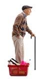 Hombre maduro que espera en línea al lado de cesta de compras Fotografía de archivo libre de regalías