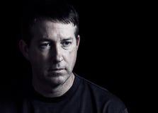 Hombre maduro que expresa emociones negativas en fondo oscuro Fotografía de archivo