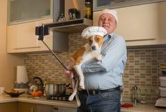 Hombre maduro que hace el selfie en una cocina con el casquillo blanco que lleva del perro lindo del basenji imágenes de archivo libres de regalías