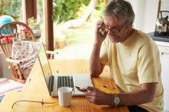 Hombre maduro que hace en la línea compra usando tarjeta de crédito Imagen de archivo