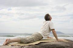 Hombre maduro que hace yoga en el mar Fotos de archivo