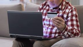 Hombre maduro que inserta número de su tarjeta de crédito en el ordenador portátil al acceso fácil de la cuenta almacen de video