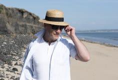 Hombre maduro que lleva un sombrero y las gafas de sol en la playa en verano Fotos de archivo libres de regalías