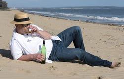 Hombre maduro que lleva un sombrero y las gafas de sol que descansan sobre la playa con una botella de vino en verano Imágenes de archivo libres de regalías