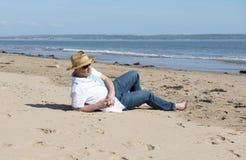 Hombre maduro que lleva un sombrero y las gafas de sol que descansan sobre la playa en verano Foto de archivo libre de regalías